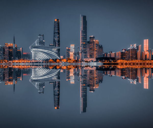 Reflection of cityscape in river at night