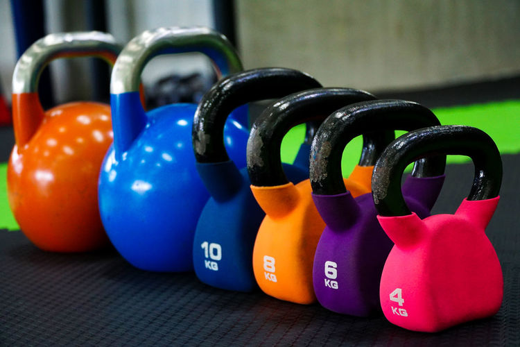 Many colorful kettlebell inside the gym. Ball Blue Choice Close-up Design Focus On Foreground Group Group Of Objects Gym In A Row Indoors  Kettlebell  Large Group Of Objects Multi Colored No People Number Shape Sport Sports Equipment Still Life Table Variation Workout This Is Strength