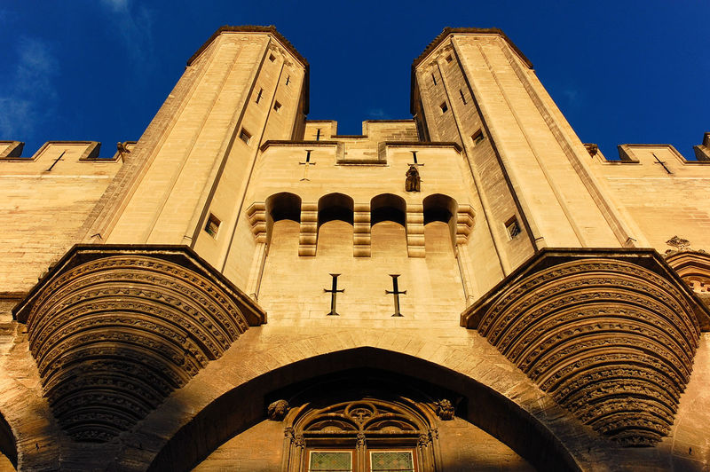 Low Angle View Of Palais Des Papes Against Blue Sky