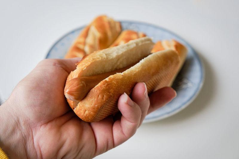 Close-up of hand holding hot-dog