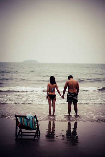 Sea Beach Water Sky Horizon Land Horizon Over Water Two People Rear View Real People Full Length Togetherness Nature Shirtless Leisure Activity Standing Men People Chair Couple - Relationship