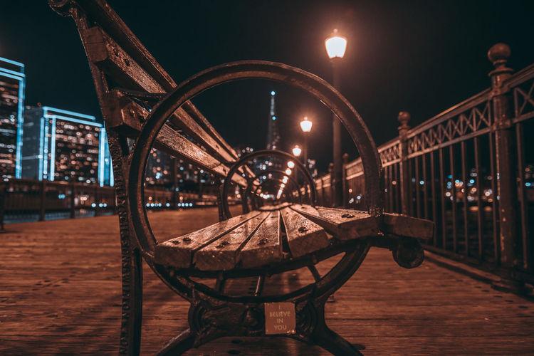 Empty bench on illuminated bridge against sky at night