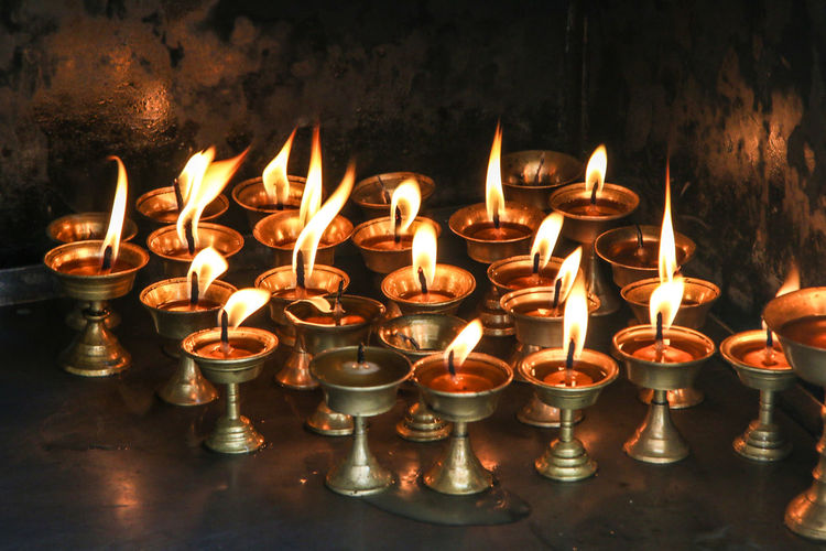 Close-up of candles burning in illuminated building