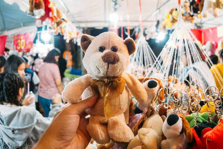 Cropped hand holding teddy bear at market