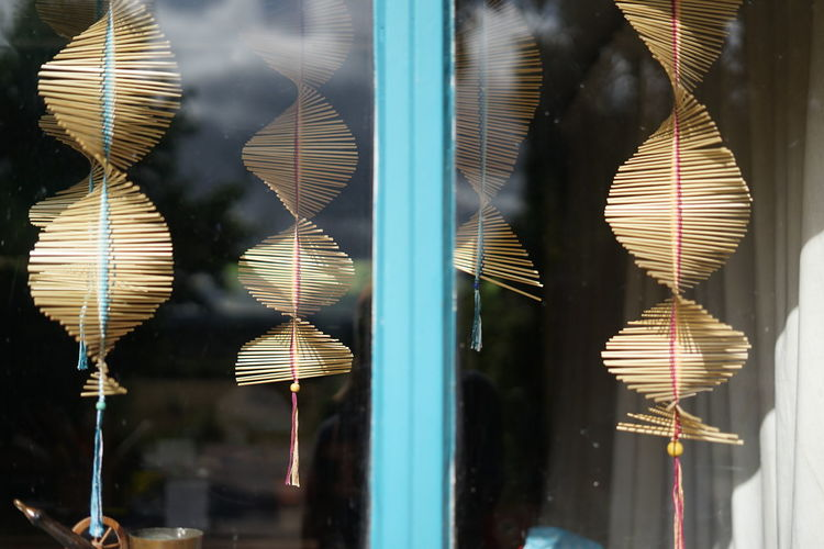 Close-up of decorations hanging on glass window
