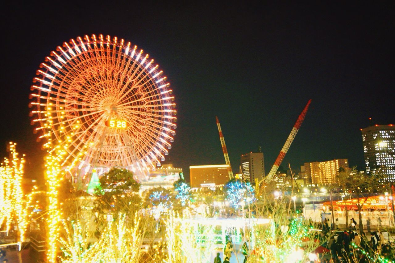 amusement park, arts culture and entertainment, night, illuminated, ferris wheel, amusement park ride, leisure activity, motion, outdoors, building exterior, clear sky, excitement, sky, architecture, city, cityscape, no people