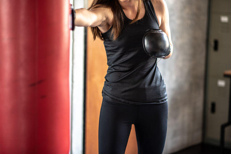 Midsection of woman practicing boxing in gym