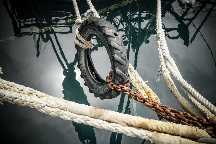 Chain Day Hanging No People Outdoors Reflections Ropes Ropes Boats Rusty Rusty Chain Strength Tire Water Water Reflections