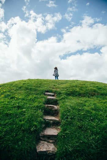 Low angle view of woman standing on grassy hill against sky