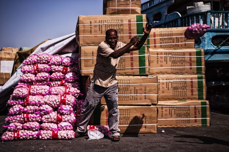The Photojournalist - 2017 EyeEm Awards Worker Boat Commercial Dock Garlic worker loading garlic in a boat at The Sharja commercial port The Street Photographer - 2017 EyeEm Awards