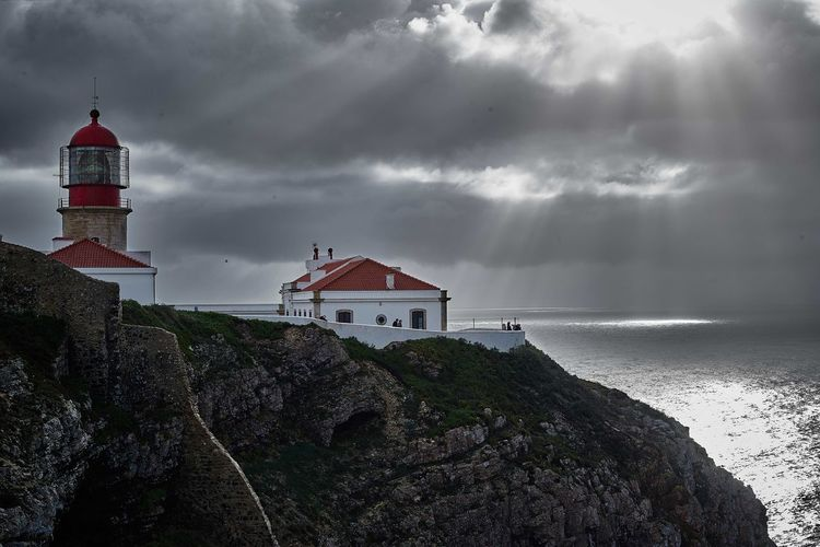Lighthouse by sea against cloudy sky