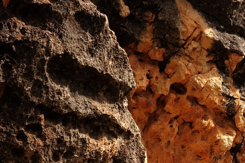 Close up of stone eroded by weather Sandstone Eroded Weathered Full Frame No People Backgrounds Rock Nature Day Rock - Object Pattern Textured  Close-up Sunlight Outdoors Solid High Angle View Rock Formation Land Rough Brown