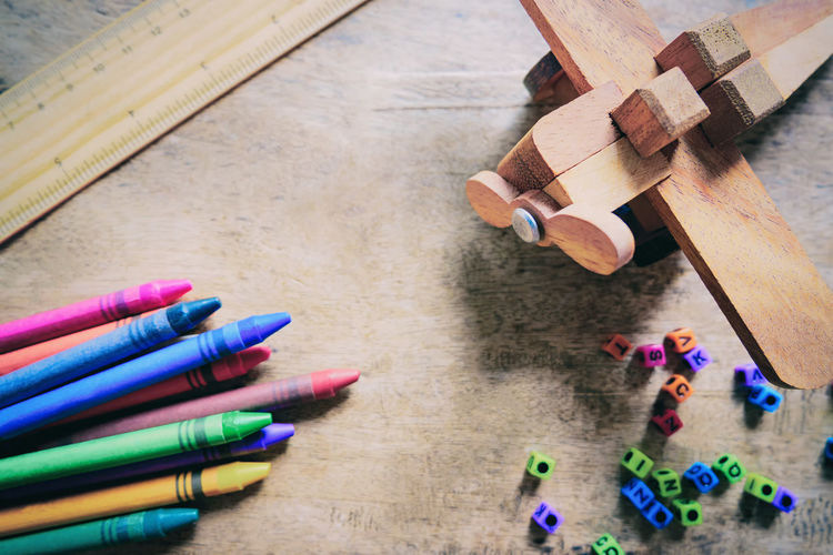 High angle view of multi colored crayons with model airplane on table