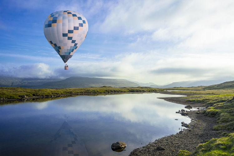 Hot air balloon flying over water against sky
