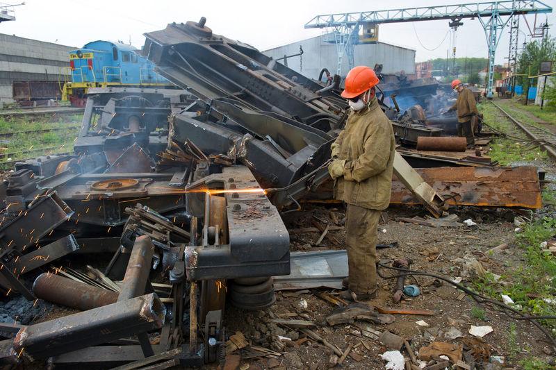 Worker welding scrap metal