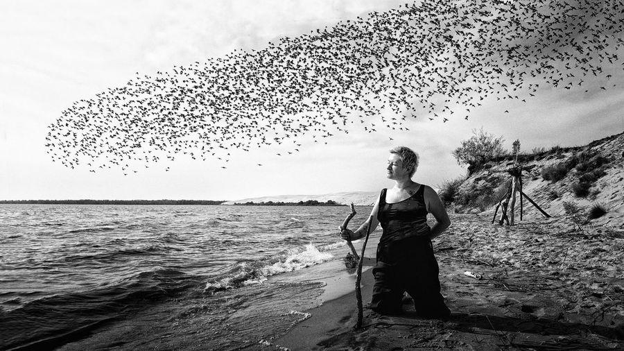 Woman kneeling at beach against birds flying in sky