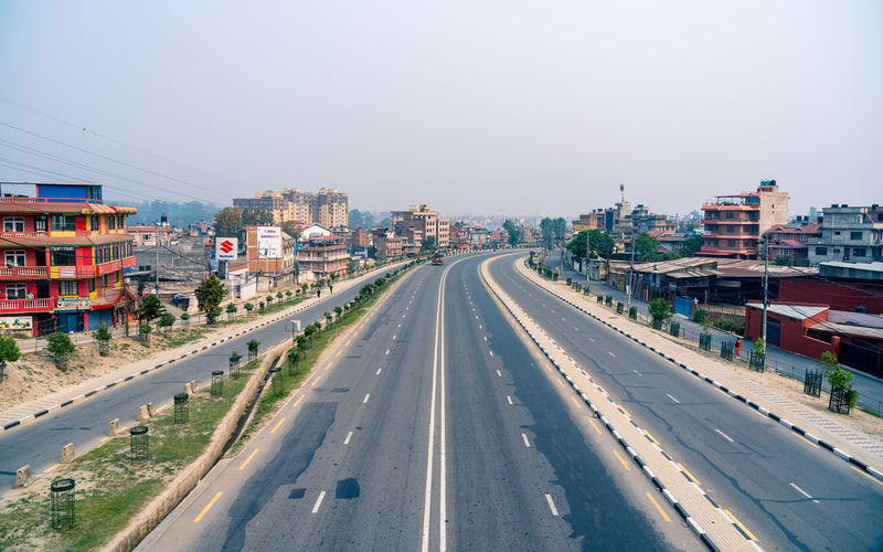 High angle view of road by buildings against clear sky