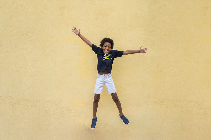 Full length portrait of happy young man jumping