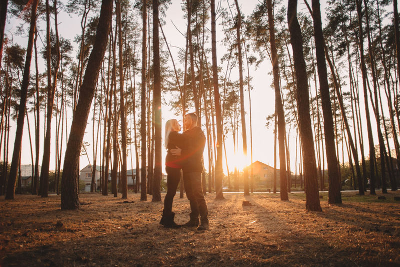 Rear view of man and woman standing by trees in forest