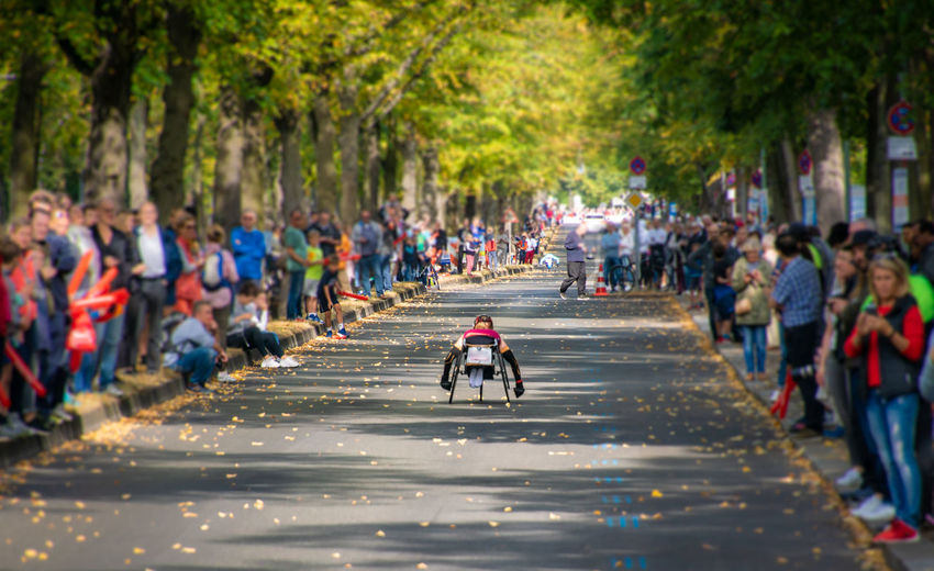 Adaptive athlete wheelchair racing on road amidst crowd
