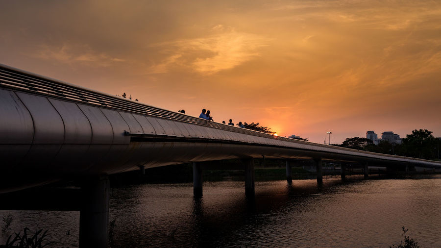 People on bridge against sky during sunset
