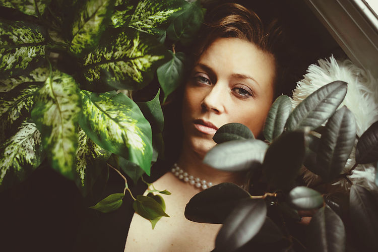 Portrait of young woman with leaves and plants in winter