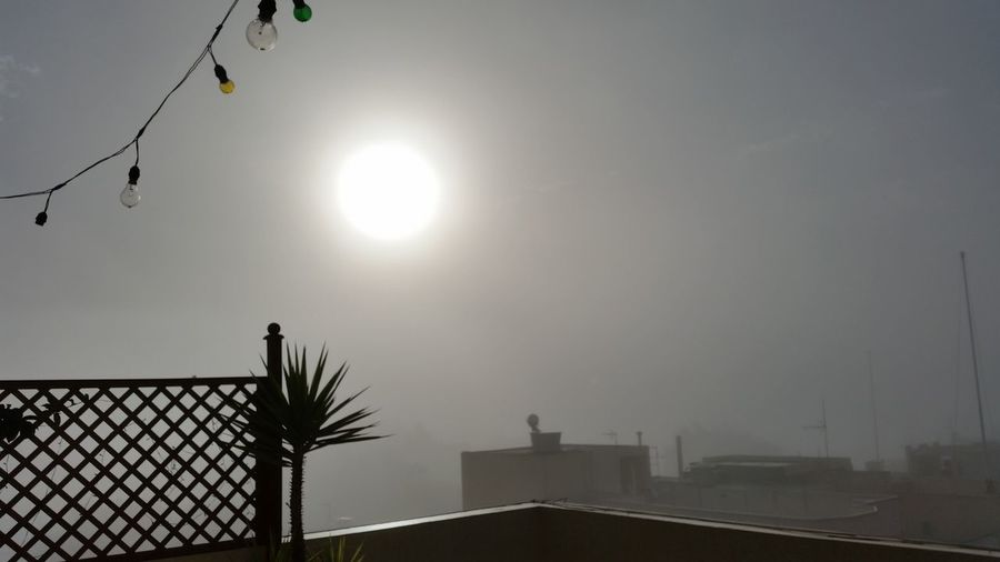 Sun shining over roofs in foggy weather