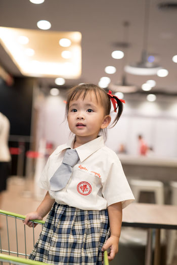 Casual Clothing Childhood Cute Day Elementary Age Focus On Foreground Front View Girls Home Interior Indoors  Innocence Leisure Activity Lifestyles Looking At Camera One Person Portrait Real People Standing