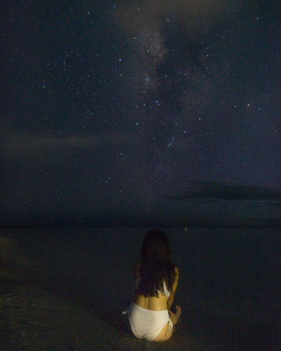 Rear view of woman sitting against sky at night