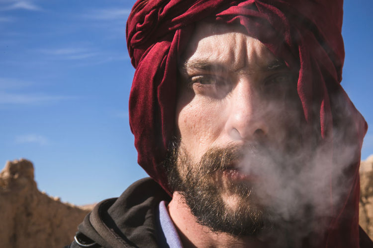 Close-up of man smoking against sky