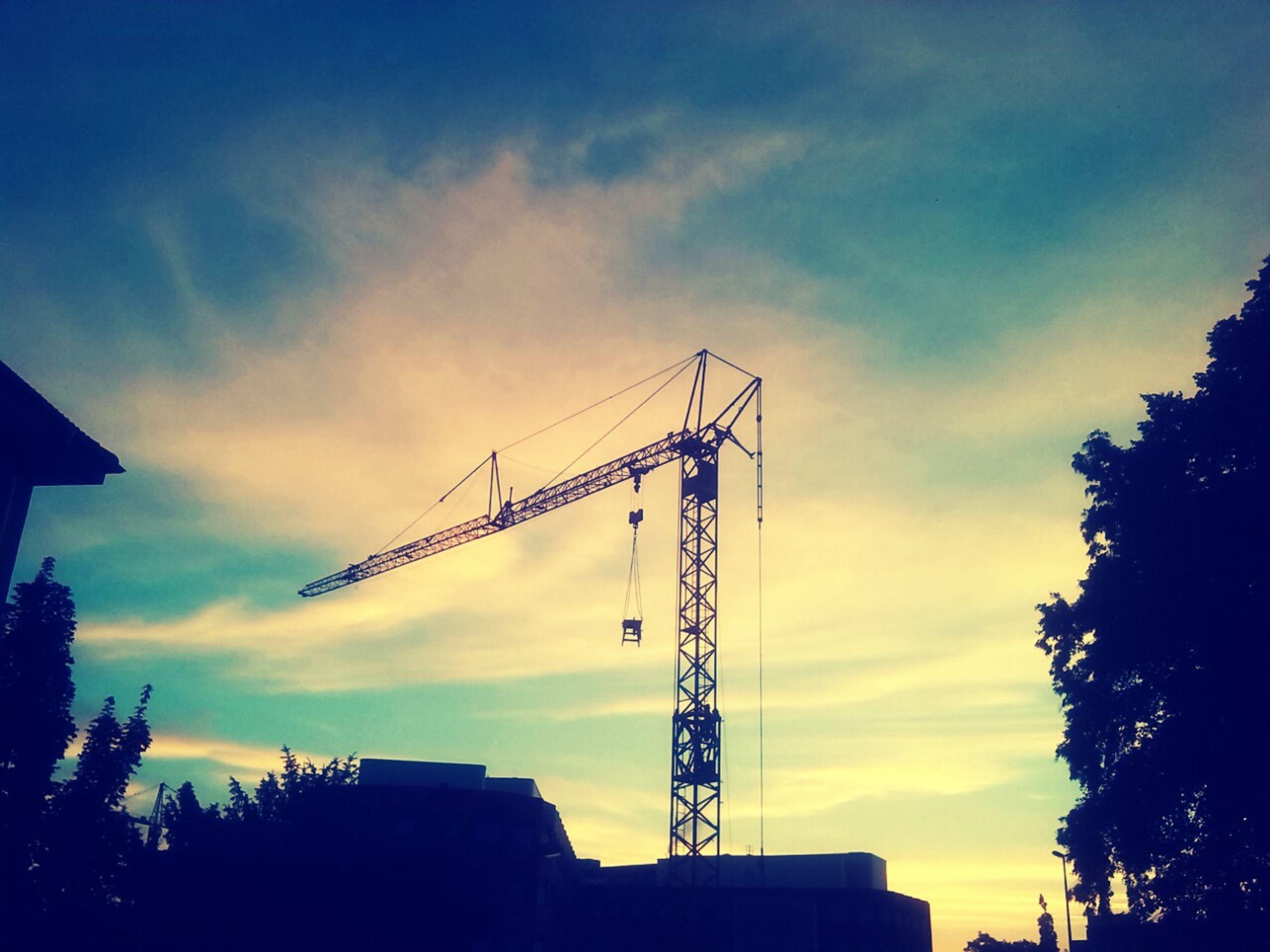sky, low angle view, silhouette, sunset, built structure, architecture, cloud - sky, building exterior, crane - construction machinery, construction site, cloud, development, dusk, crane, cloudy, outdoors, no people, connection, construction, tree