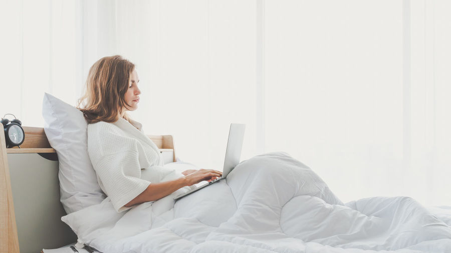 Young woman using mobile phone while sitting on bed at home