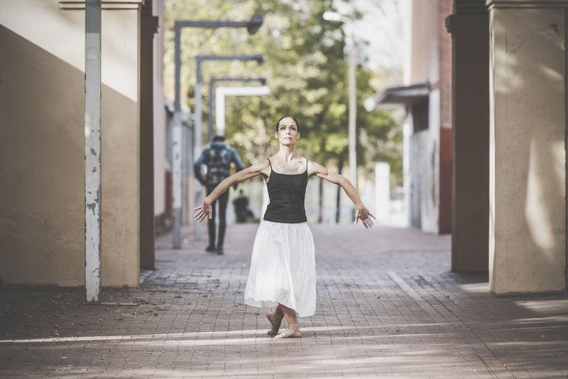 Full length of woman dancing on footpath