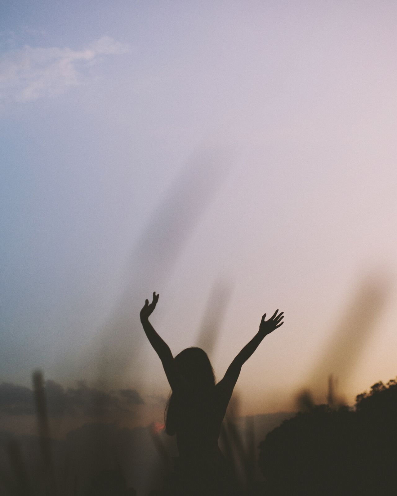 Silhouette of woman with arms raised against sky