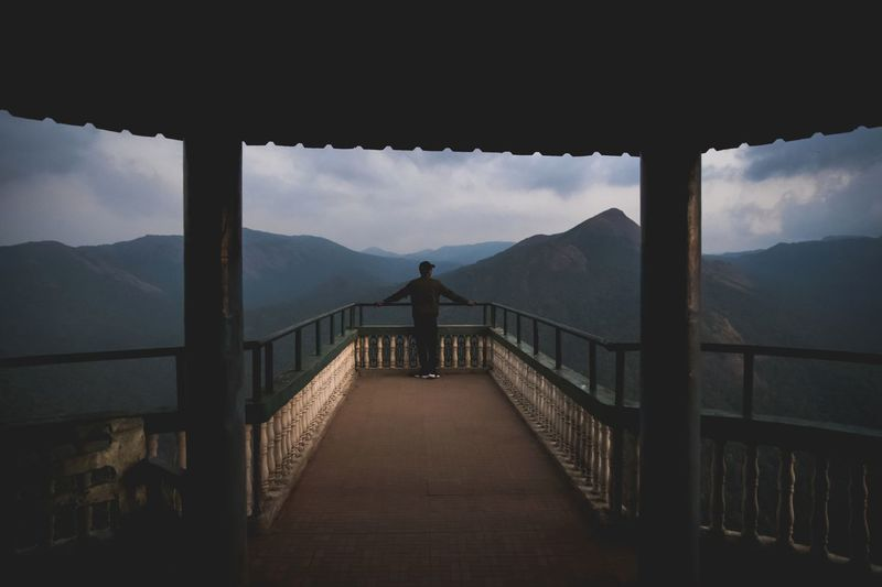 Man standing at lookout tower against mountain range