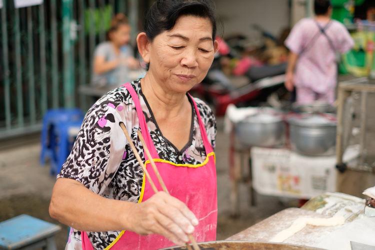 Senior woman wearing apron preparing food at market stall