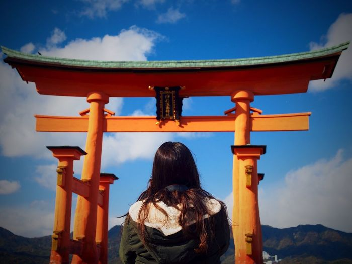 Low Angle View Of Woman Looking At Torii Gate