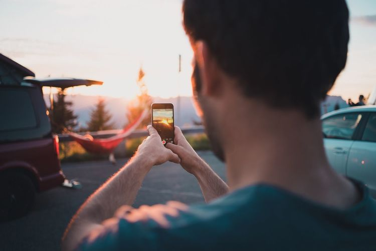 Taking a picture of the sunset Taking A Picture Sunset Freedom Live Authentic Car Transportation Smart Phone Mode Of Transport Land Vehicle Wireless Technology Portable Information Device Mobile Phone Car Interior Communication Real People Journey Photographing Travel Cellphone Road Trip Windshield Photography Themes Technology