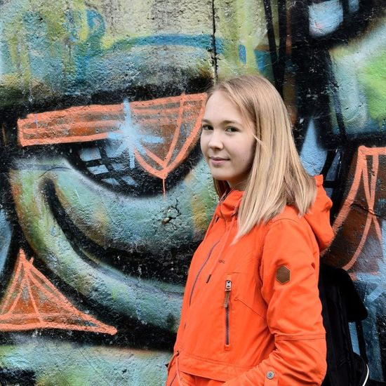Graffiti One Person Casual Clothing Street Art Young Adult Young Women Smiling Real People Standing Happiness Outdoors Day Portrait Multi Colored Beautiful Woman Medium-length Hair People Lifestyles Front View The Portraitist - 2017 EyeEm Awards