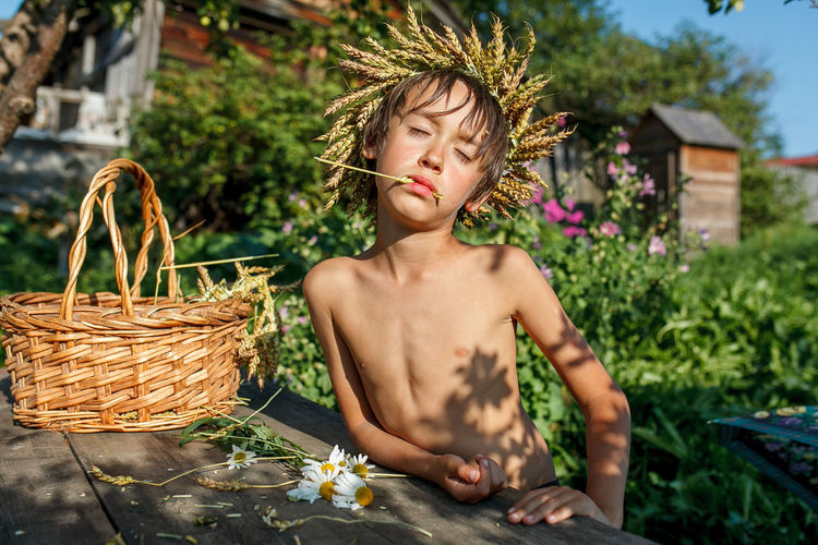 Shirtless boy eating cereal by basket against plants