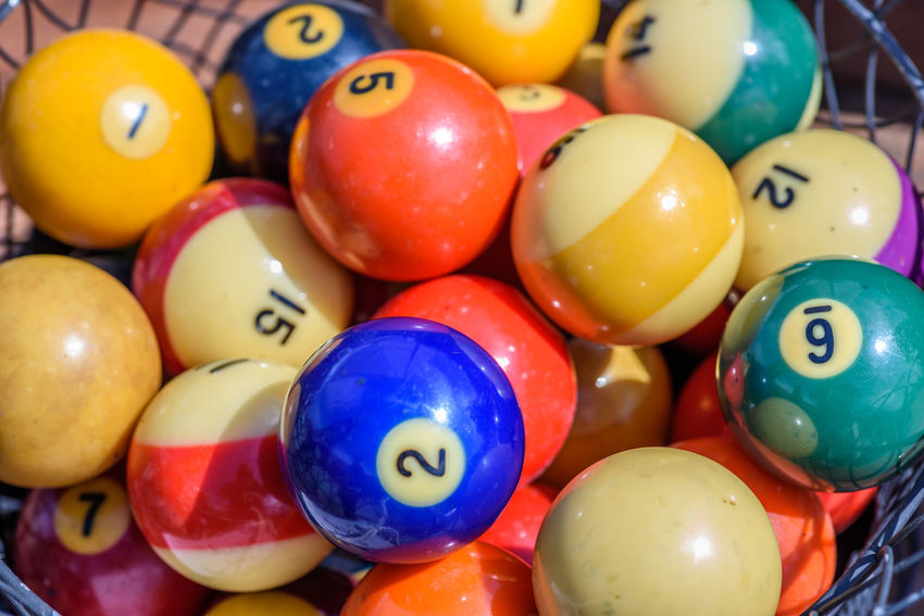 Vintage pool balls in wire basket on sunny day Pool Balls Billiard Balls Retro Style Numbers Striped Colorful Rustic Style Vintage Style Antiques Photography Antiques Games Sport Leisure Activity Basket Outdoors Antique Fair No People Sunny Day