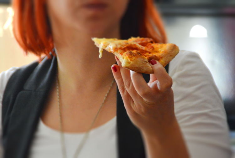 Close-up Eating Food Food And Drink Holding Human Hand Indoors  Lifestyles Midsection One Person Pizza Ready-to-eat Real People SLICE Unhealthy Eating Woman Young Adult