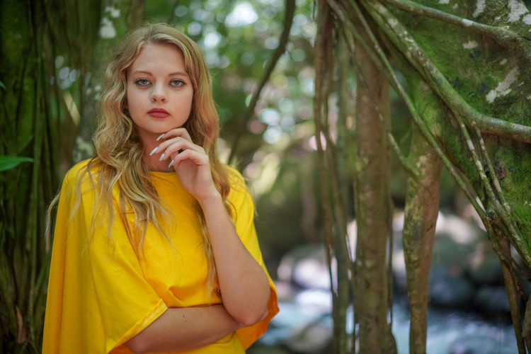 Portrait of beautiful woman against trees