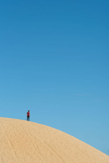 Low angle view of man standing on sand dune against blue sky