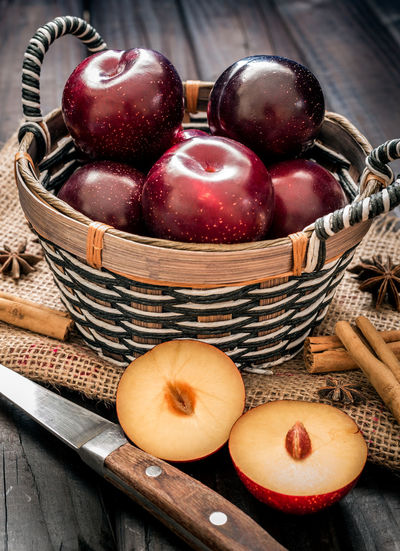 Plums on wooden table Red Wwod Basket Close-up Food Food And Drink Freshness Fruit Healthy Eating Indoors  No People Plum Table Wooden