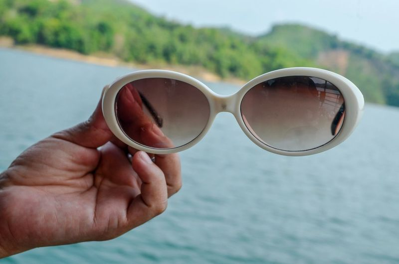 Cropped hand of person holding sunglasses over sea