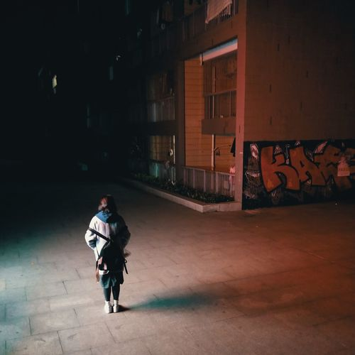 Full Length Of Woman Standing On Footpath At Night