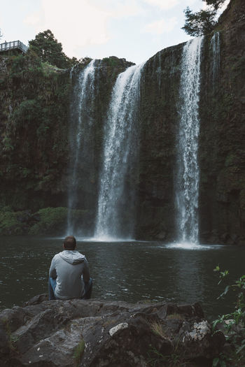 Rear view of man sitting on rock against waterfall