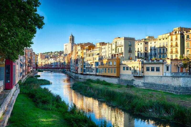 Canal amidst cityscape against clear sky