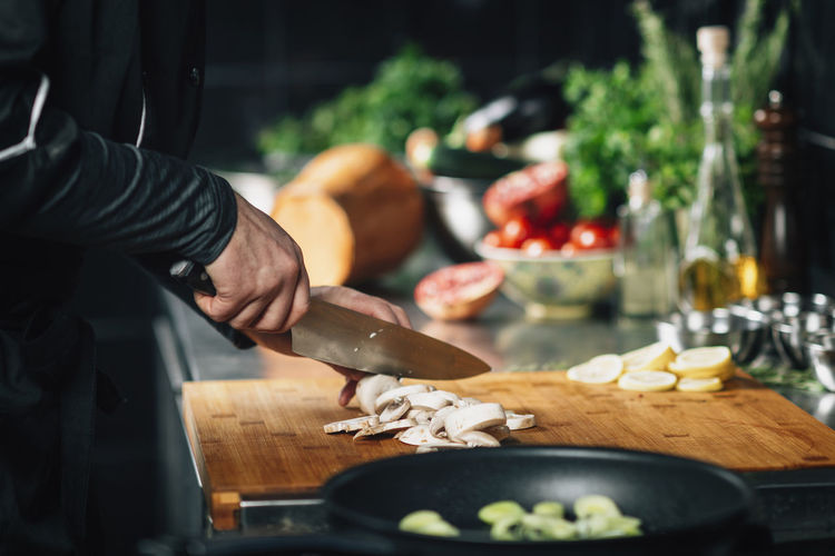 Cooking dinner - chef holding a knife, cutting mushrooms on a wooden cutting board